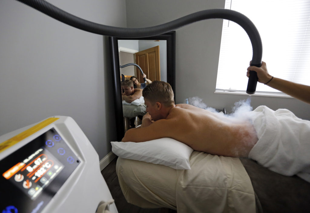 Morgan Saunders performs a localized cryotherapy session on the lower back of Luke King at Chill Cryotherapy in Gahanna on Aug. 24, 2015. Saunders used vaporized nitrogen to lower the skin temperature below 30º F. (Adam Cairns / The Columbus Dispatch)